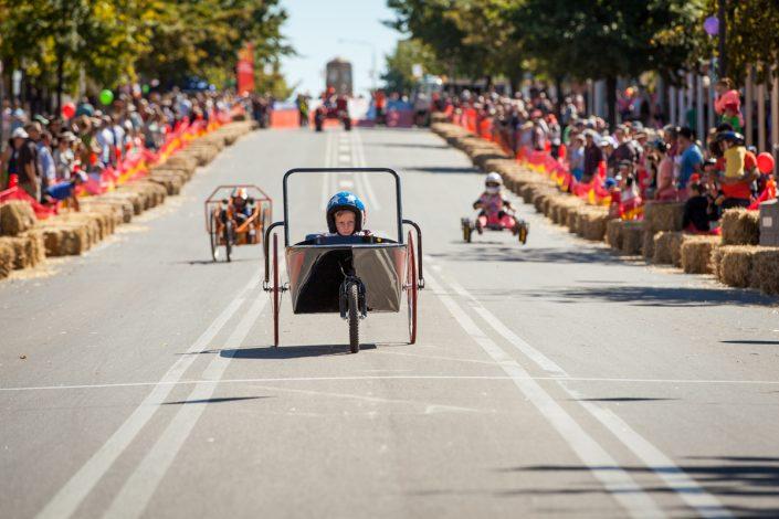Boy racing billy cart down main street Australian Billy Cart Championships at corowa
