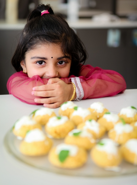 butanese girl overlooks biscuits made by butanese family for cookbook called hungry